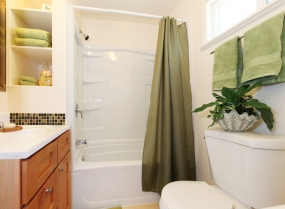 White and green bathroom with tub and cabinet.