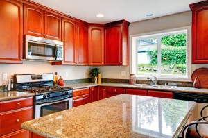 Light tones kitchen room with cherry wood cabinets, marble counter tops and modern appliances