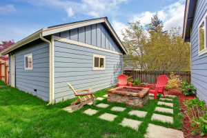 Small backyard with shed and patio area. View of brick fire pit and deck chairs