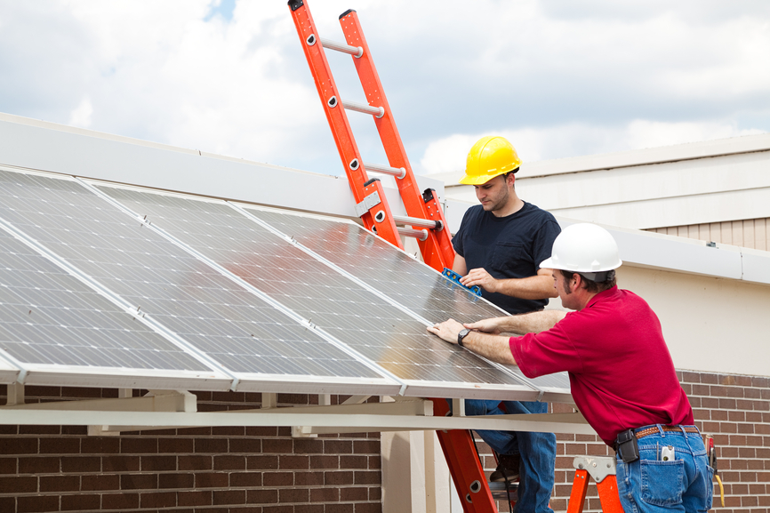 inspecting energy efficient solar panels on the roof of a building.