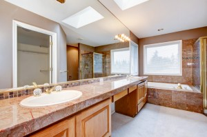 Large lnew uxury bathroom with red granite countertops and tub