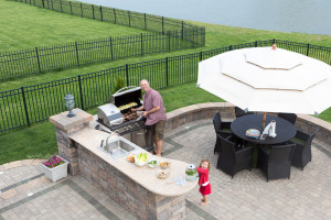 Father and daughter preparing a barbecue at an outdoor summer kitchen on a paved patio with a garden umbrella table and chairs as they grill the meat on the gas BBQ waiting for guests to arrive