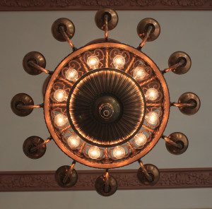 antique copper hanging light fixture shot from the ground looking up